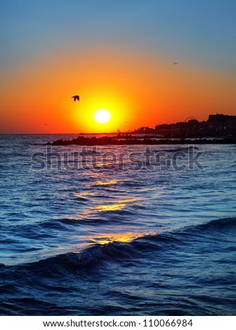 sunset on the sea with waves - stock photo