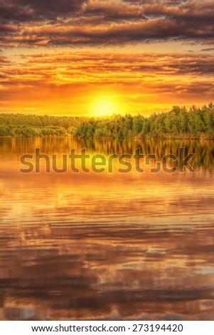 Sunset on the shore of beautiful lake - stock photo