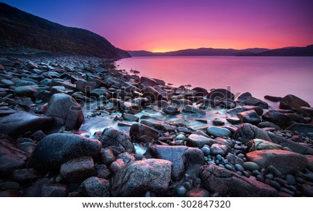 Sunset on the stone coast - stock photo