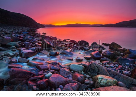 Sunset on the stone coast and river - stock photo