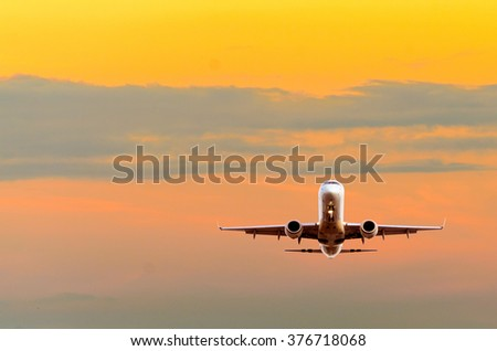 Sunset or sunrise (dawn, dusk ) flight of the airplane (jet) over beautiful sky and ocean. - stock photo