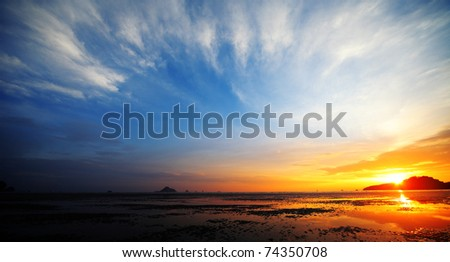 Sunset over a beach during low tide - stock photo