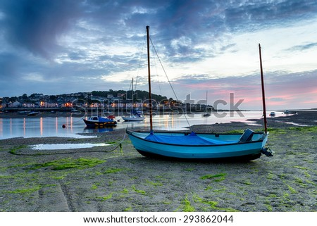 Sunset over a blue boat on the beach at Instow, looking out at the pretty fishing village of Appledore just outside of Bideford on the Devon coast - stock photo