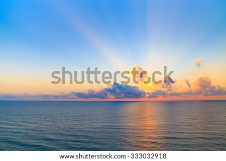 Sunset over a calm ocean casting beams of orange light into the air as the setting sun penetrates the clouds above in a scenic tranquil seascape. - stock photo