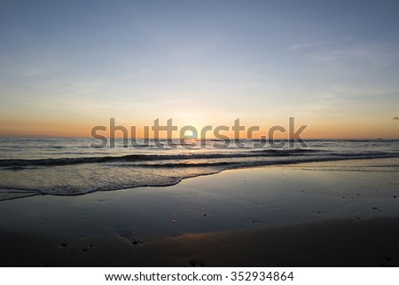 Sunset over a calm ocean during low tide in the Philippines - stock photo