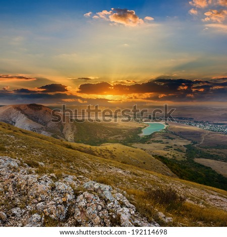 sunset over a dry hills - stock photo