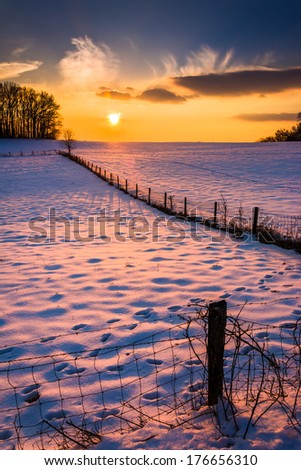 Sunset over a fence in a snow covered farm field in rural Carroll County, Maryland.