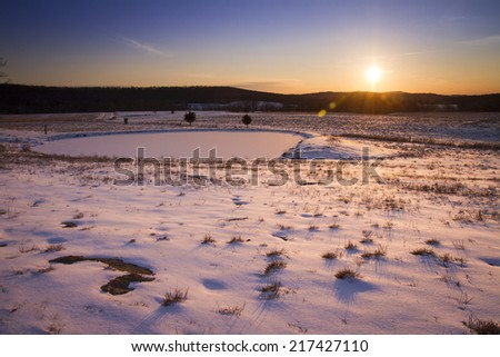 Sunset over a frozen pond on a farm. - stock photo