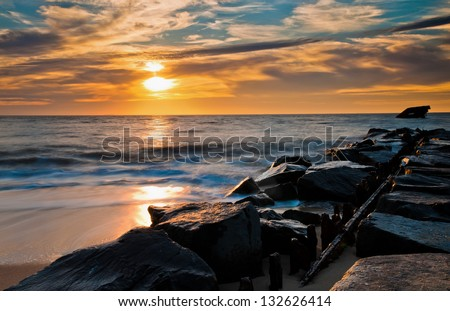 Sunset over a jetty and the USS Atlantus Shipwreck at Sunset Beach, Cape May, New Jersey. - stock photo