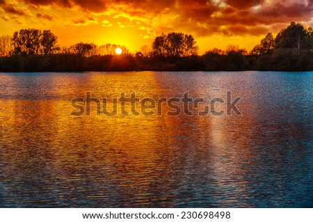 Sunset over a lake  in the winter - stock photo