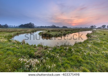 Sunset over a meander in the lowland Regge river, Twente Netherlands. A meander forms when moving water in a stream erodes the outer banks and widens its valley. - stock photo