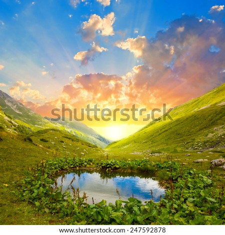sunset over a mountain lake - stock photo