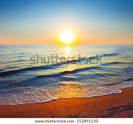 sunset over a quiet sea beach - stock photo