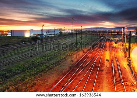 Sunset over a railroad with many tracks - stock photo