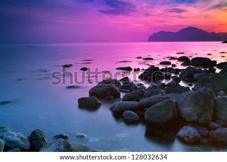 Sunset over a rocky coast - stock photo