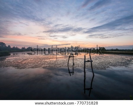 Sunset over a shrimp farm lake in eastern Thailand