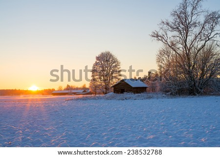 Sunset over agricultural landscape in winter at sunset - stock photo