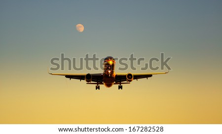 Sunset over an airport with the moon visible and a plane coming in for landing.