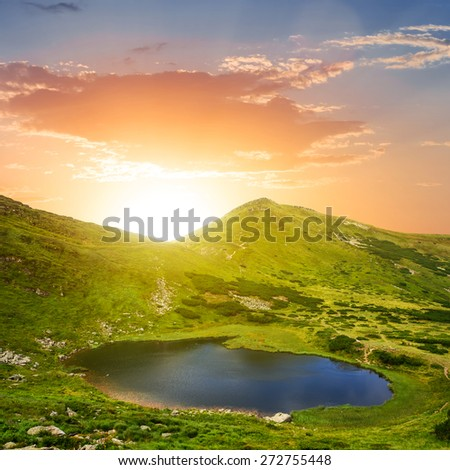 sunset over an emerald mountain lake - stock photo
