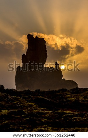 Sunset over an oceanfront landscape shows very moody, dark terrain framed by a tall protruding reef and sunlight casting orange light rays.
