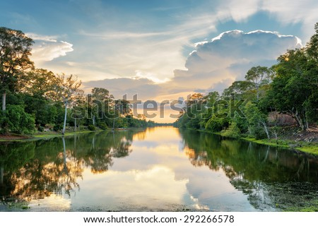 Sunset over ancient moat surrounding mysterious ruins of Angkor Thom in Siem Reap, Cambodia. Angkor Thom is a popular tourist attraction. - stock photo