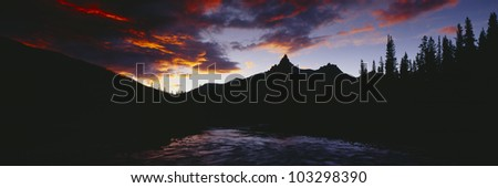 Sunset over aspens and Bear Tooth at Pilot Mountain, Wyoming - stock photo