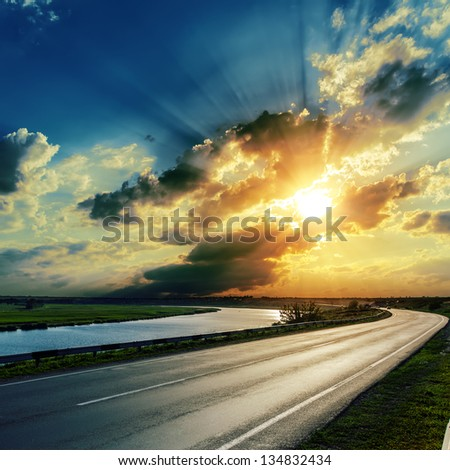 sunset over asphalt road and river - stock photo