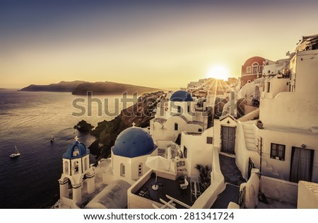 Sunset over blue dome churches of Santorini, Greece - stock photo