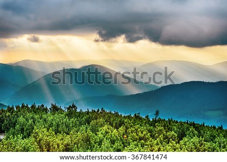 Sunset over blue mountains. Sun with sunbeams shining through the clouds - stock photo
