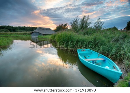 Sunset over boat houses on the Norfolk Broads at Hickling Broad in Norfolk