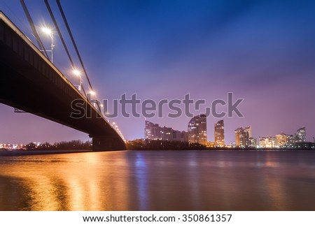 Sunset over bridge and river in city. Kiev, Ukraine