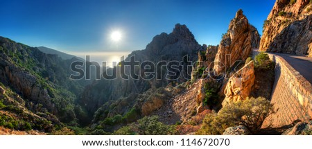 Sunset over Calanques de Piana with road through mountains in foreground, Corsica, France.