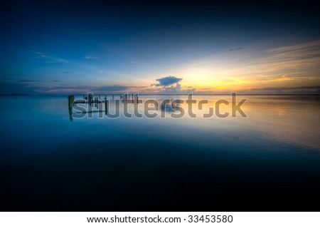 Sunset over calm Caribbean waters in Rock Sound, Eleuthera. - stock photo
