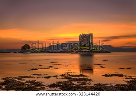 Sunset over Castle Stalker, Highlands, Scotland, United Kingdom. Long exposure and hdr processed. - stock photo