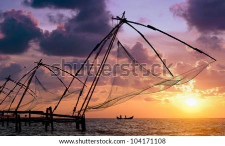Sunset over Chinese Fishing nets and boat in Cochin (Kochi), Kerala, India. - stock photo