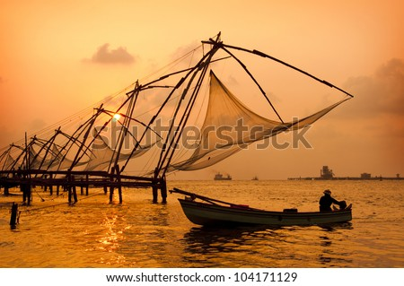 Sunset over Chinese Fishing nets and boat in Cochin (Kochi), Kerala, India.