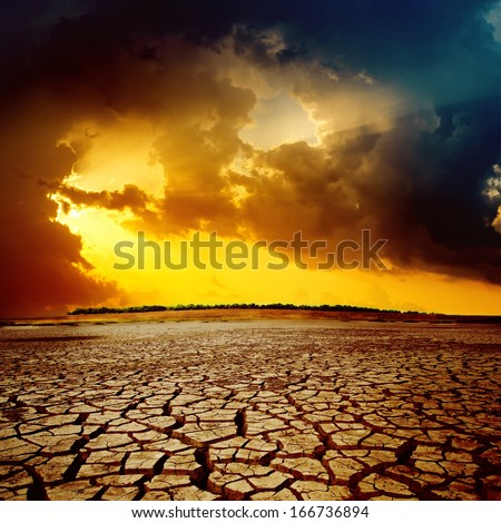 sunset over cracked desert - stock photo