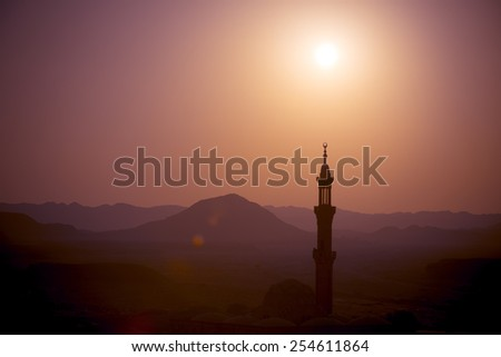 Sunset over desert with muslim mosque in the foreground - stock photo