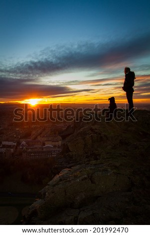 Sunset over Edinburgh, with woman and dog, cliff edge, Salisbury Crags