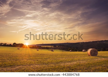 Sunset over farm field with hay bales in Czech republic