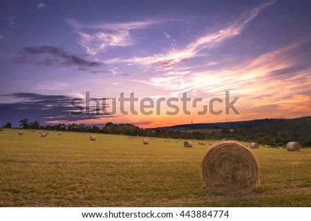 Sunset over farm field with hay bales in Czech republic - stock photo