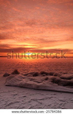 Sunset over frozen lake in winter, Finland - stock photo