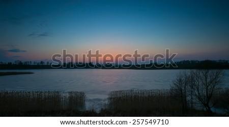 sunset over frozen lake on masuria lake district - stock photo