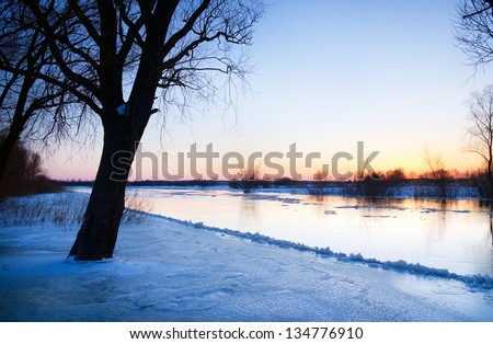 Sunset over frozen river in winter - stock photo