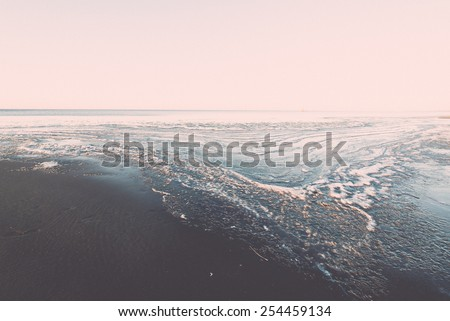 sunset over frozen sea with ice blocks and dramatic colorful sky - vintage retro grainy film effect - stock photo