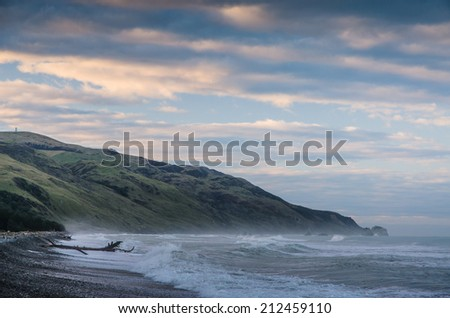 sunset over harsh sea shore - stock photo