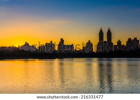 Sunset over Jacqueline Kennedy Onassis Reservoir and buildings in the Central Park West Historic District, at Central Park, Manhattan, New York.
