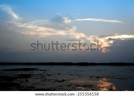 Sunset over lake in Asia stormy weather global warming - stock photo