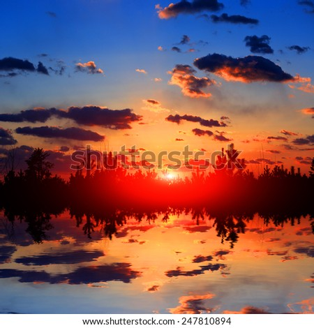 Sunset over lake in forest - stock photo