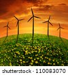 sunset over meadow with wind turbines - stock photo